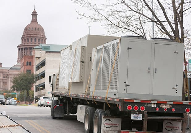 unit strapped on back of transport truck to Travis County Executive Office Building